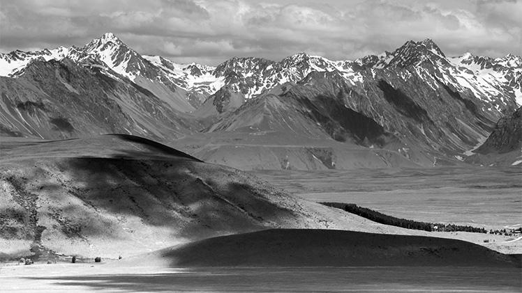 長焦鏡頭把遠處的山跟近的草地「壓縮」,形成像在同一平面上的效果。
